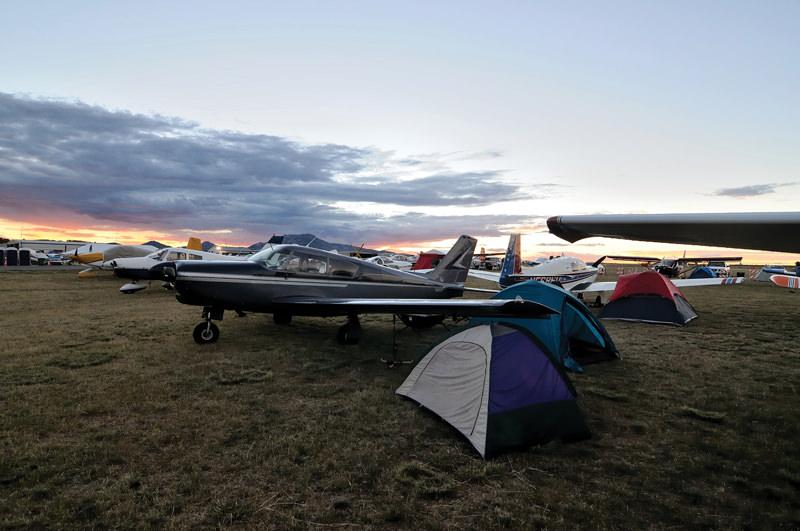Sun sets beyond the large aircraft camping area at the Prescott Fly In