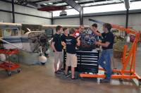 Mike Zidziunas (right) works on an aircraft engine with students and members of the Lakeland Aero Club.